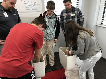Students learn to adjust toilet bowl components