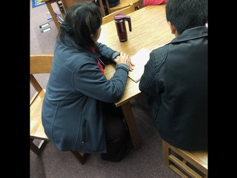 Mrs. Gonzalez working with her students on research