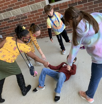 students helping another student up