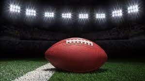 Image of a football on the field with lights in the background.