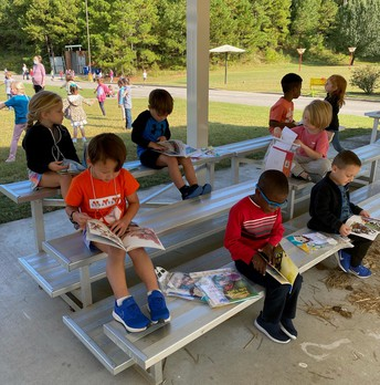 Children sitting on risers in outdoor classroom