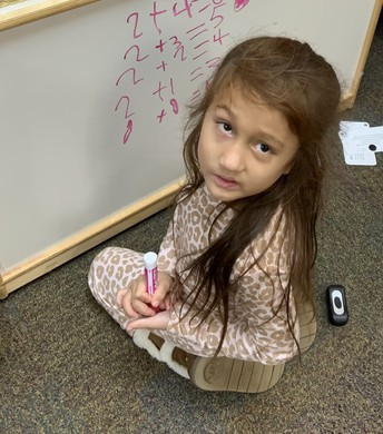 Kindergarten student kneeling on the floor in front of a white board with math problems