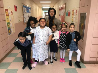 Ms. Morin and students from her first grade class dressing up as though they're 100 years old.