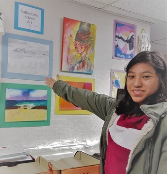 Kelly Garcia Pointing to her Latest Artistic Creation