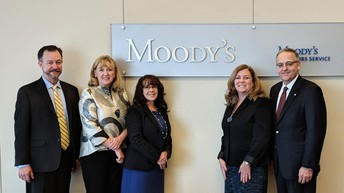 Image shows five people standing by a sign that reads Moody's.