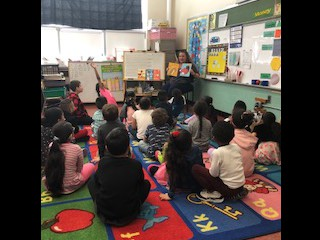 Mrs. Labossiere reads to Mrs. Donth's class