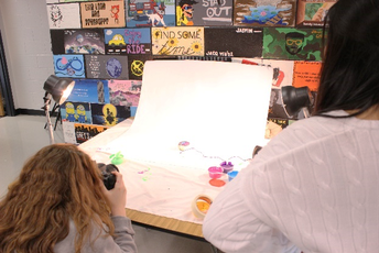Image of a student taking a picture of their artwork