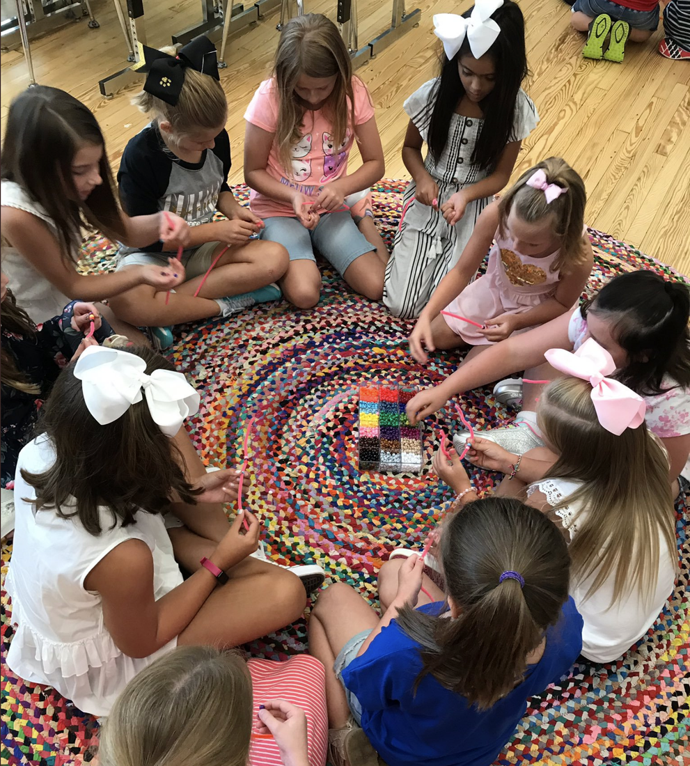 girls threading beads at EES