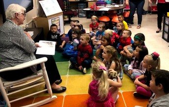 Students enjoy listening to a story from Principal-for-a-Day guest.