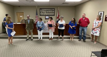 Superintendent Dr. Neill recognizing 6 employees at a school board meeting
