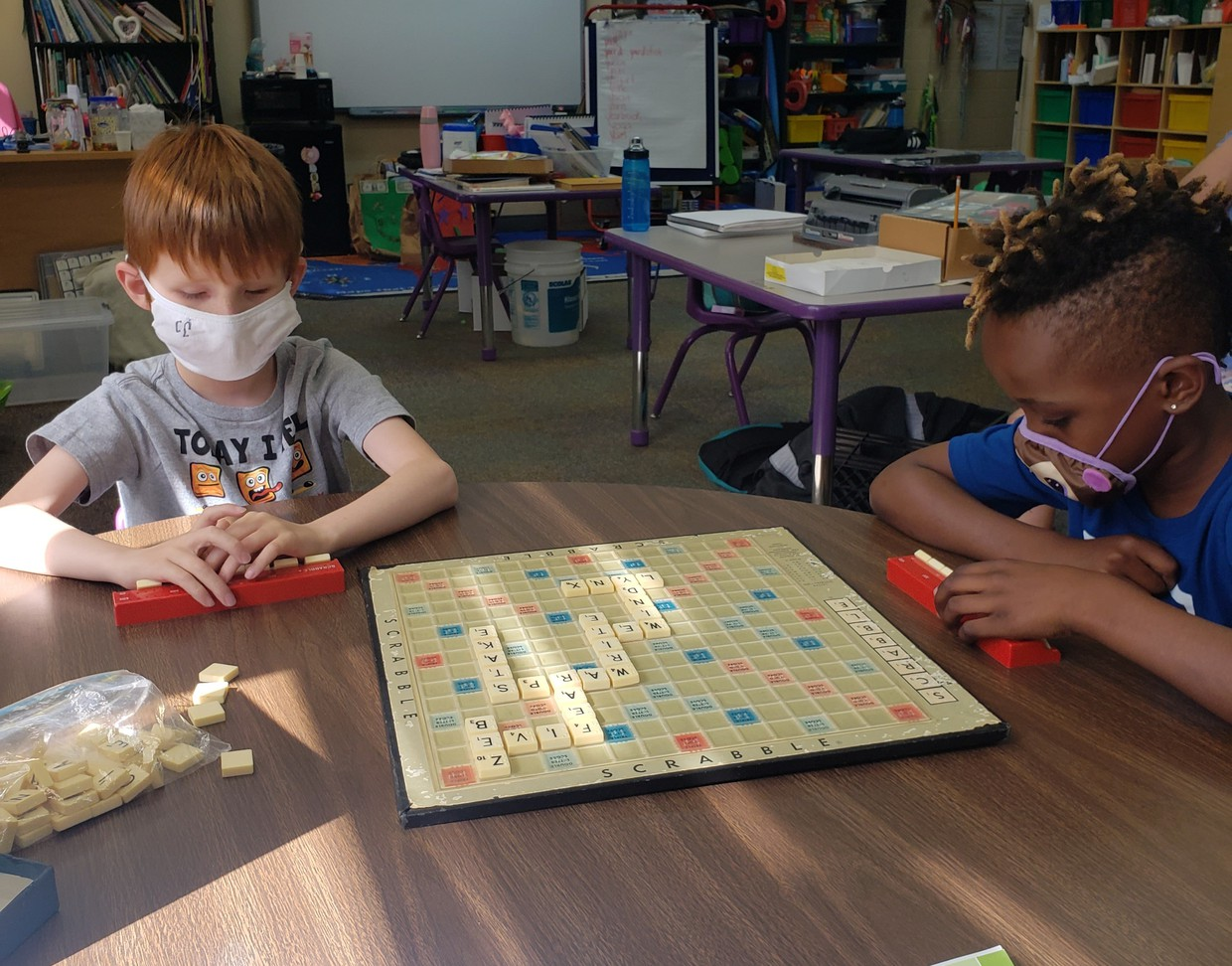 2 students sit at a table playing Scrabble. Some of the words they've used are five, zeb, and warps