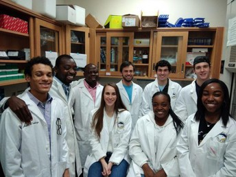 Group of Eric Gato's lab group in white lab coats, smiling. The group of nine people is diverse in both race and gender, with three women and five people of color.