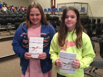 Two students proudly displaying their new books
