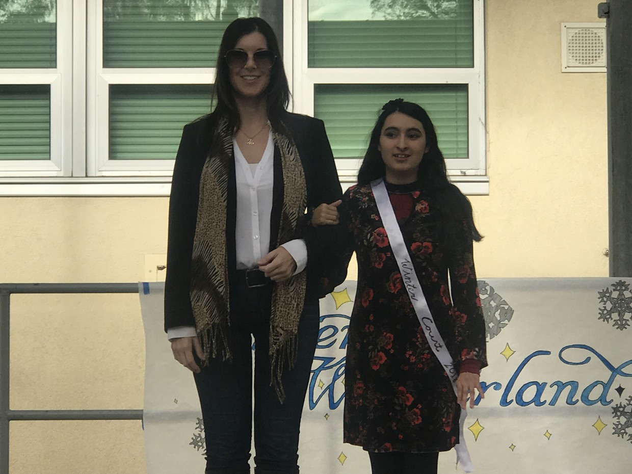 Winter Court Queen candidate, Alanis, stands proudly with her teacher Ms. Alcanero at Friday's pep assembly.