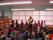 2nd graders play musical instruments with storyteller, Decee Cornish