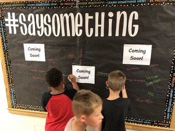 Students signing the #Say Something board