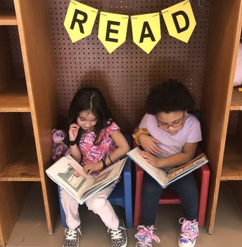 Two students reading in a cozy cubby.