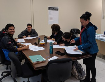 Group of students filing out their applications for internships.