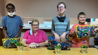 3 students stand at a table with their many creations of pillows and plants in pots; Dorm staff member sits at the table with them