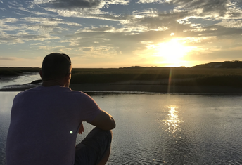 Man in the foreground looking out over a river with the sun rising in the distance.