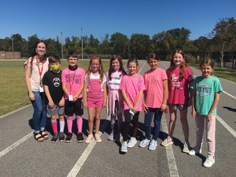 students wearing pink standing on the track
