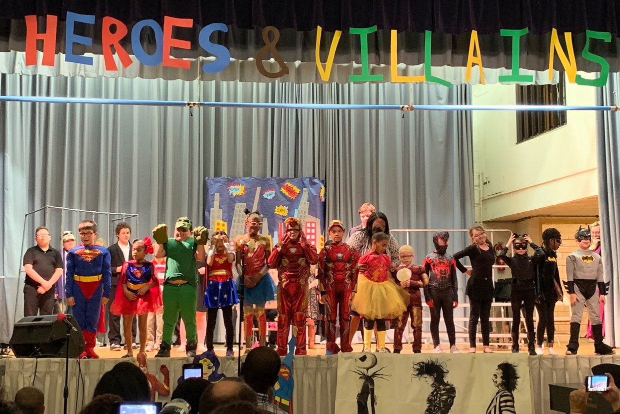 Elementary students stand on the stage in Scarberry Hall, many of them wearing super hero costumes such as Superman, Wonder Woman, etc. during the 2019 Spring Concert, Heroes & Villains.