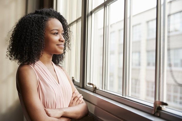 Young woman thinking with smile looking out of window