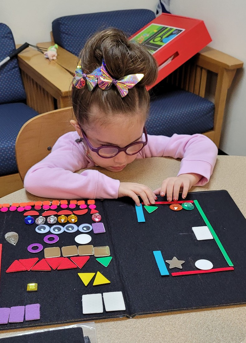 Mackenzie sits at the table creating and exploring her office map; thick black board has various shapes and colors representing items in the office