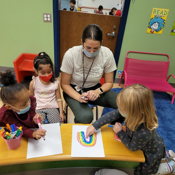 A small group of students works with a teacher on a rainbow drawing.