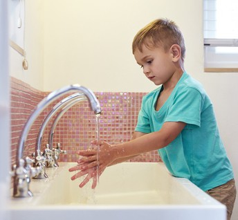 Young boy washing hands at school