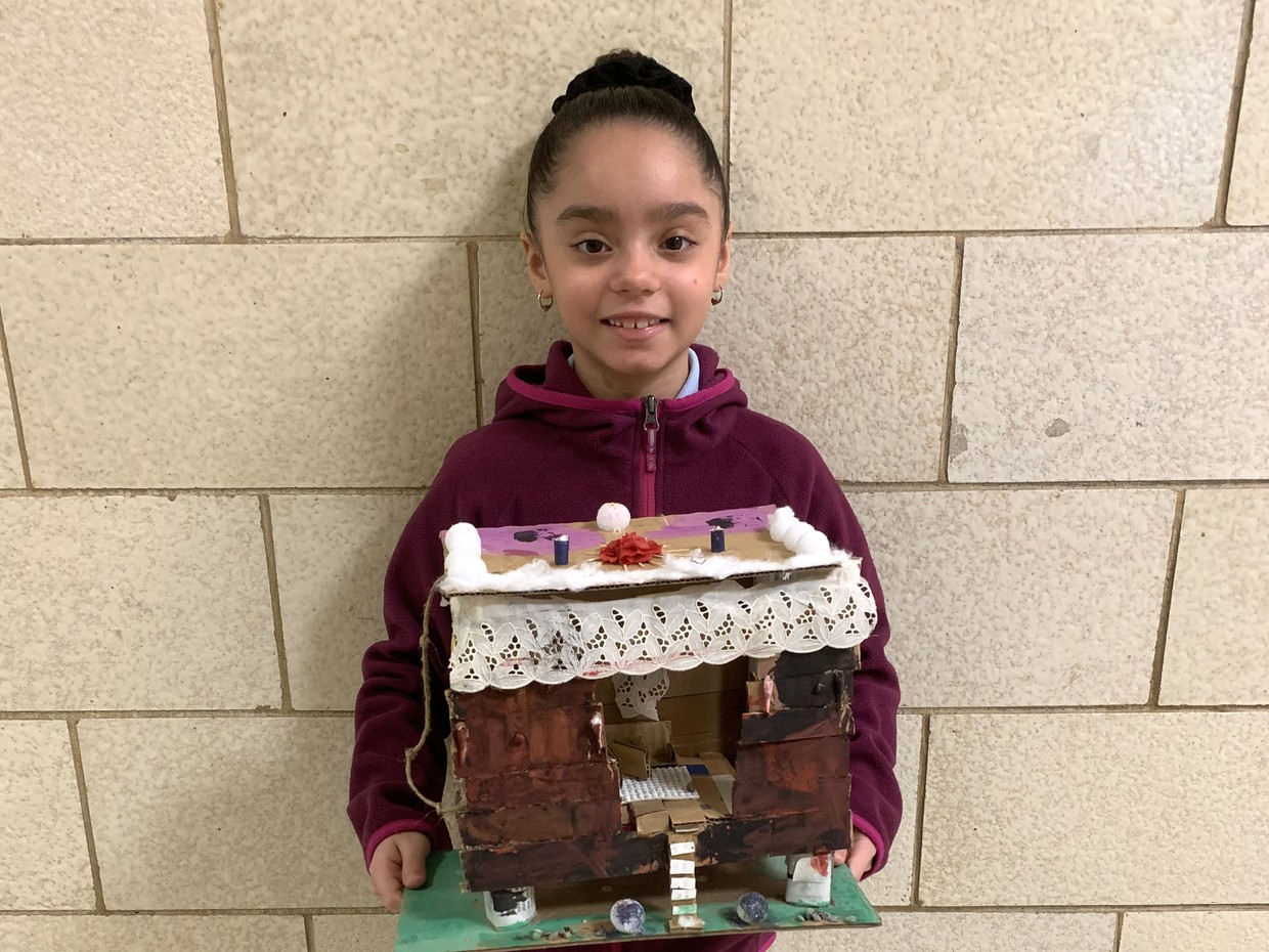 Student showing off her tree house art project.