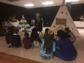 Students listened to a read aloud by the camp fire