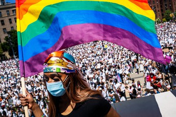 Young black woman holds Pride flag before a crowd, wearing a medical mask