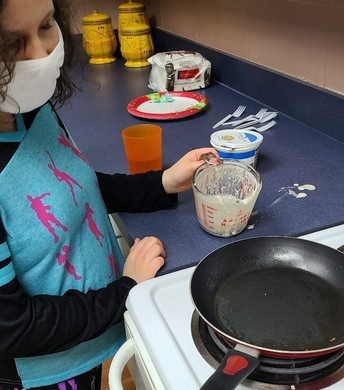 Student preparing to pour pancake batter into a pan