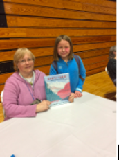 A student poses with Earth Verse author Sally M. Walker