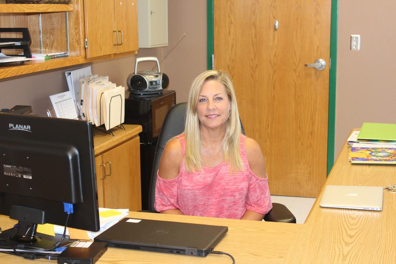 Ms. Kari Pride sitting at desk