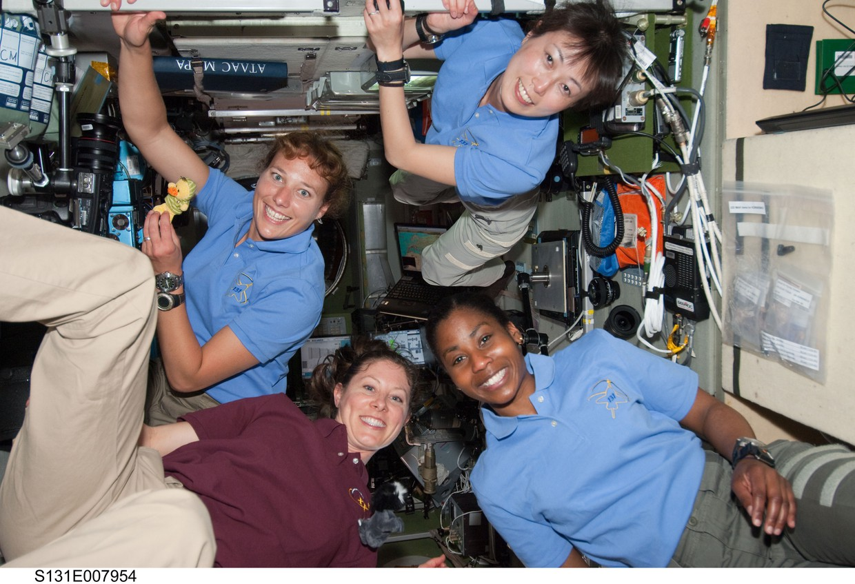Diverse group of four women astronauts on the International Space Station in polo shirts, floating in antigravity.