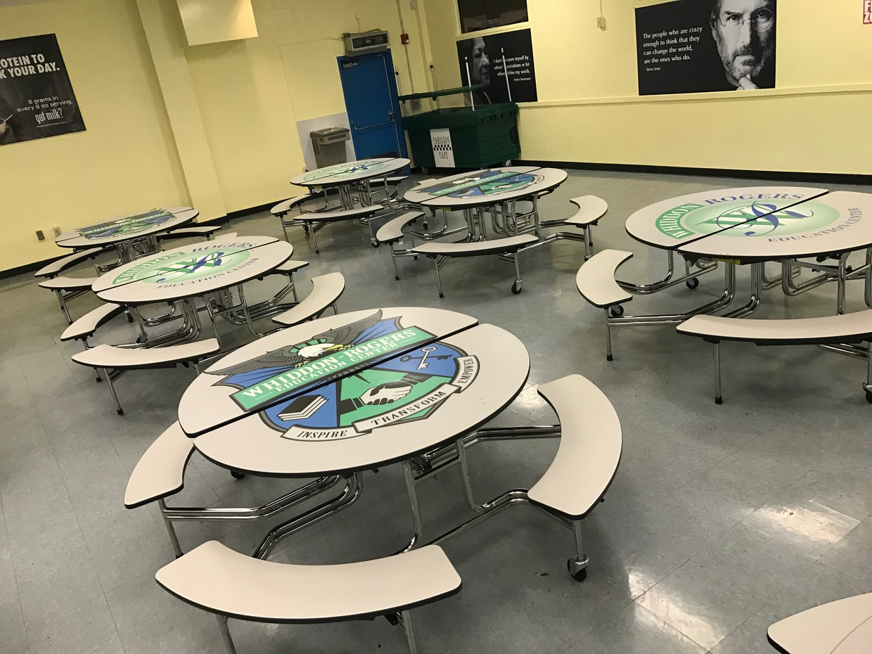 Cafeteria tables with the Whiddon-Rogers logo on them