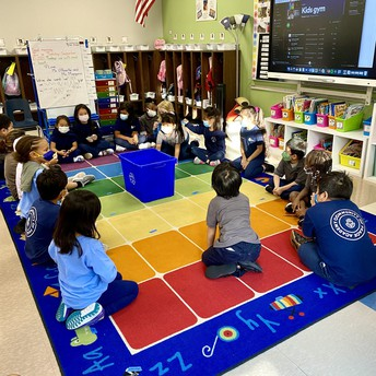 Students sit in a circle playing a game.