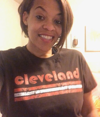 A photo of Lorrie Melton- a selfie taken in her home, she is wearing a brown Cleveland T-shirt