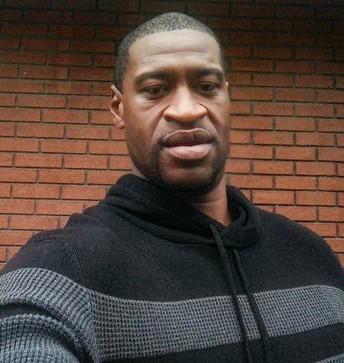 George Floyd (black male) wearing a sweater. Brick wall background.