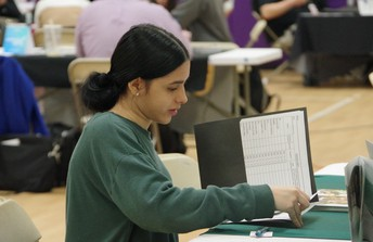 Female senior handing in paperwork at the MCAC event