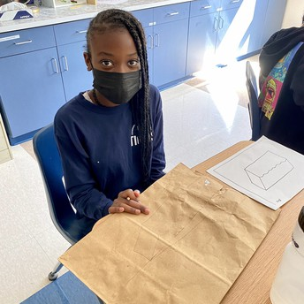 A student works on creating a parfleche container