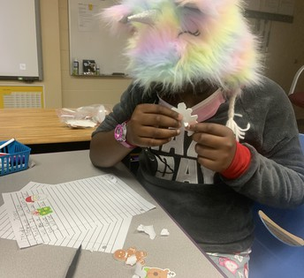 Student with a colorful fuzzy hat on with a story handwritten with several raised stickers