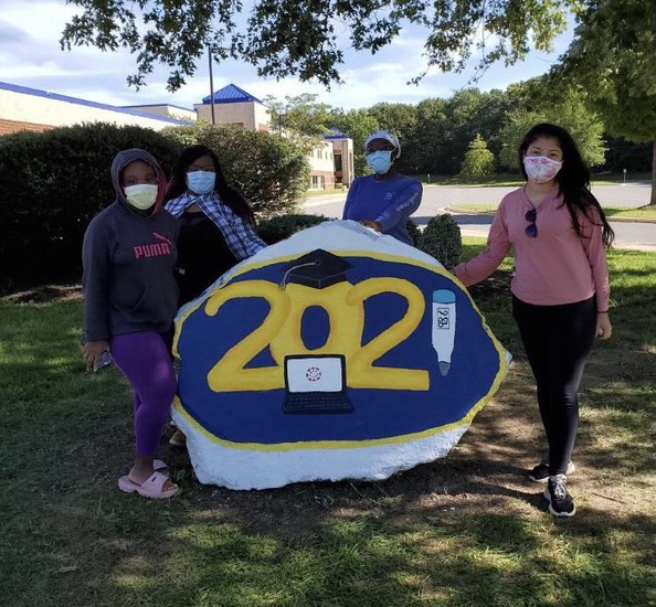 four female students wearing masks standing by 2021 rock