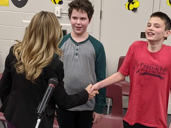 District Curriculum Supervisor Dr. Kelly Moran congratulating Chardon Middle School Spelling Champ (right) Cash Johnson and Runner-Up (left) Aidan Gerlica.