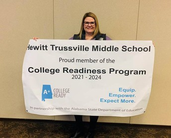Principal Jennifer Abney holds A+College Ready banner