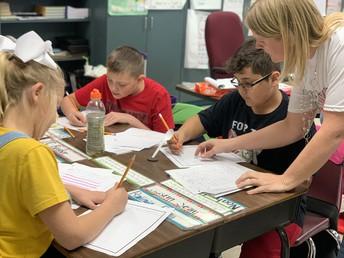 La Sra. Hayes ayuda a los estudiantes con sus escritos.