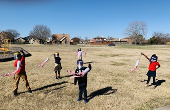 1st Grade Meteorologist test wind direction with their wind socks.