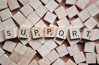the word SUPPORT spelled in wooden tiles